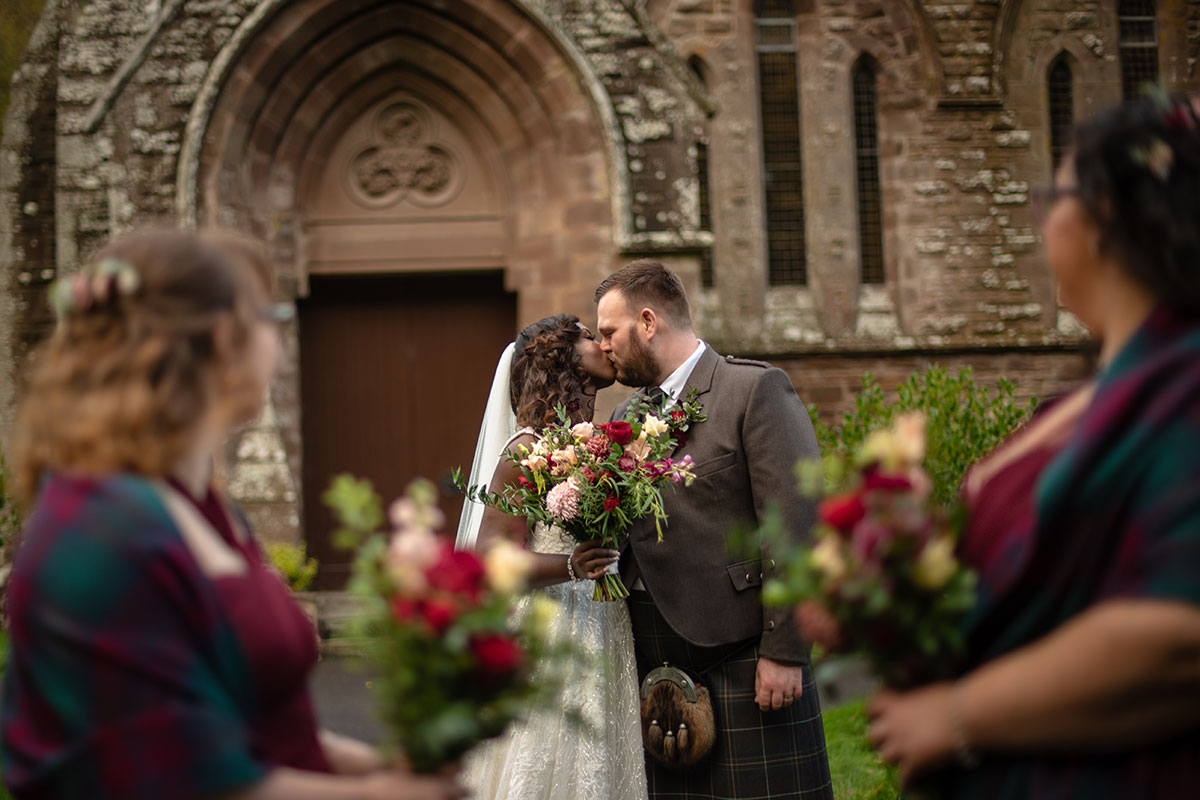 bride and groom kissing outside church with two bridesmaids in foreground