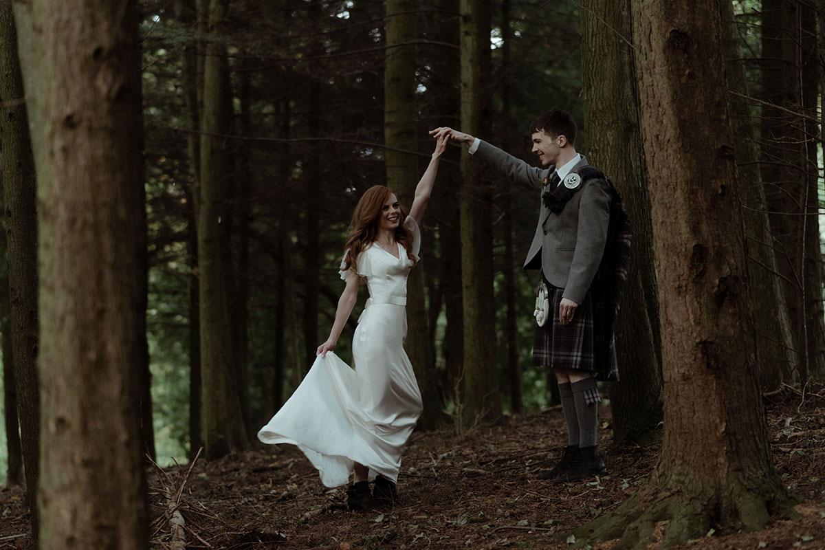 groom twirling bride dancing in woodland at Borthwick castle