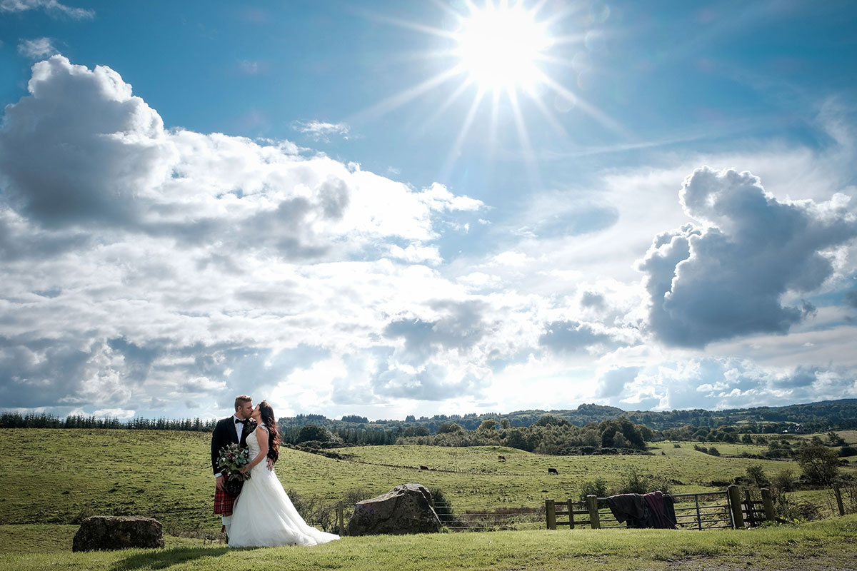 landscape image of bride and groom kissing on farmland at South Barlogan Farm with blue sky and sunshine
