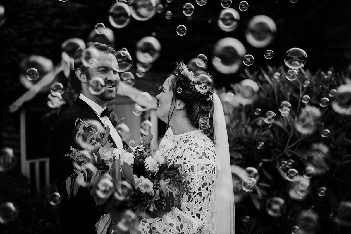 black and white image of bride and groom with lots of bubbles at relaxed Covid Edinburgh garden wedding ceremony