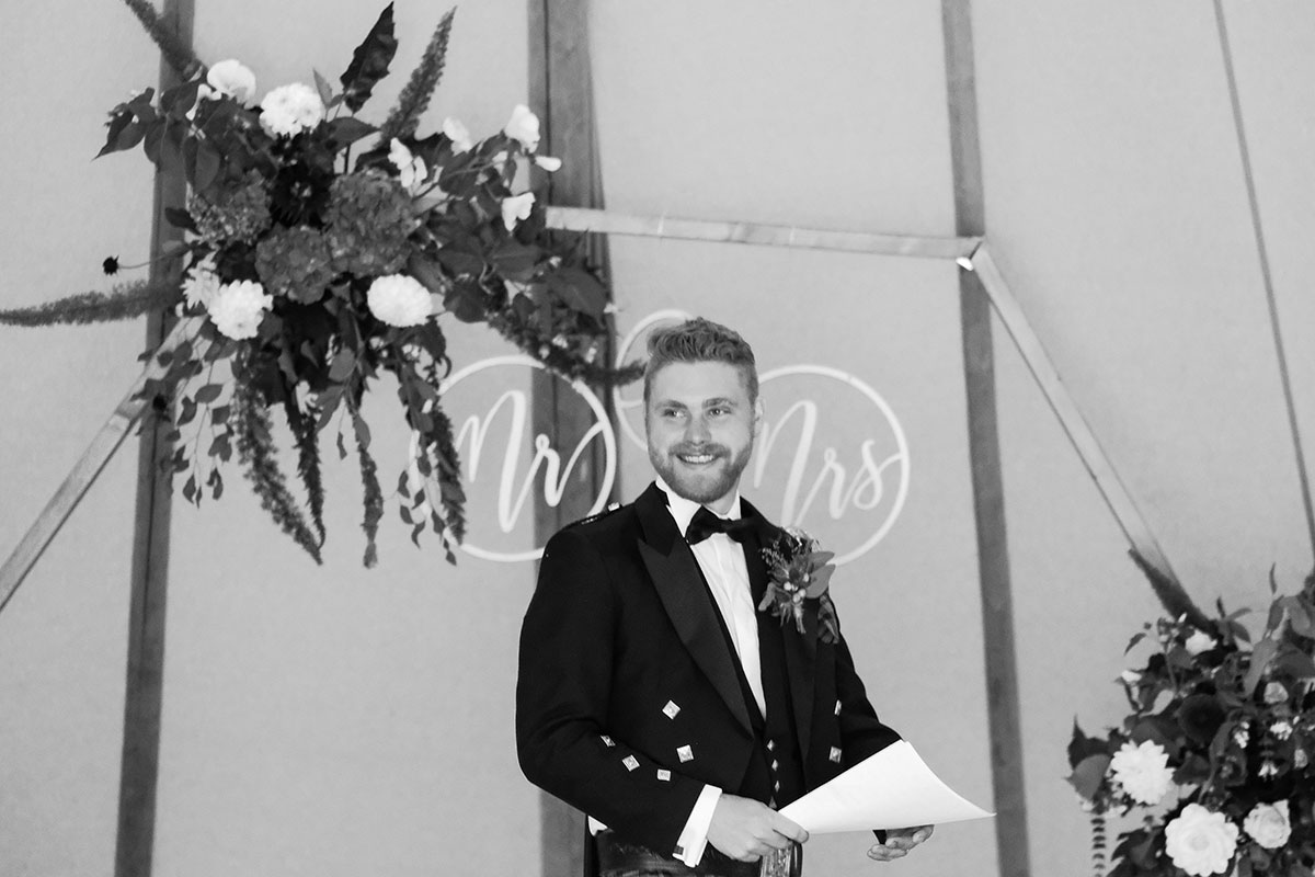 black and white image of groom doing speech in Below Canvas wedding tipi at South Barlogan Farm