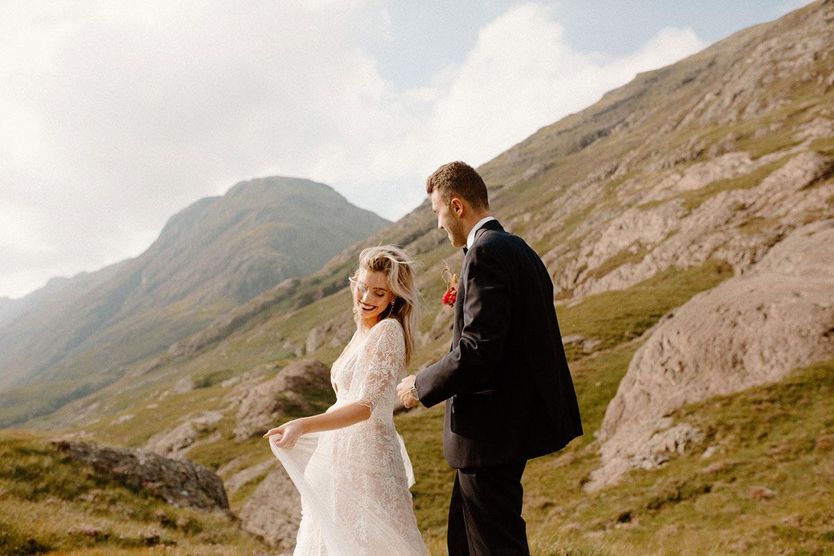 bride and groom walking on mountainside in Glen Coe