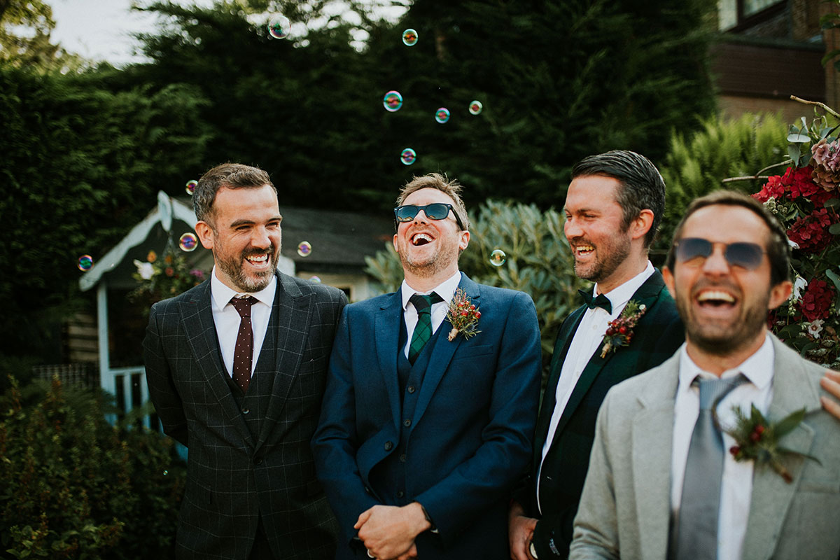 groom and three male wedding guests laughing at back garden wedding in Edinburgh