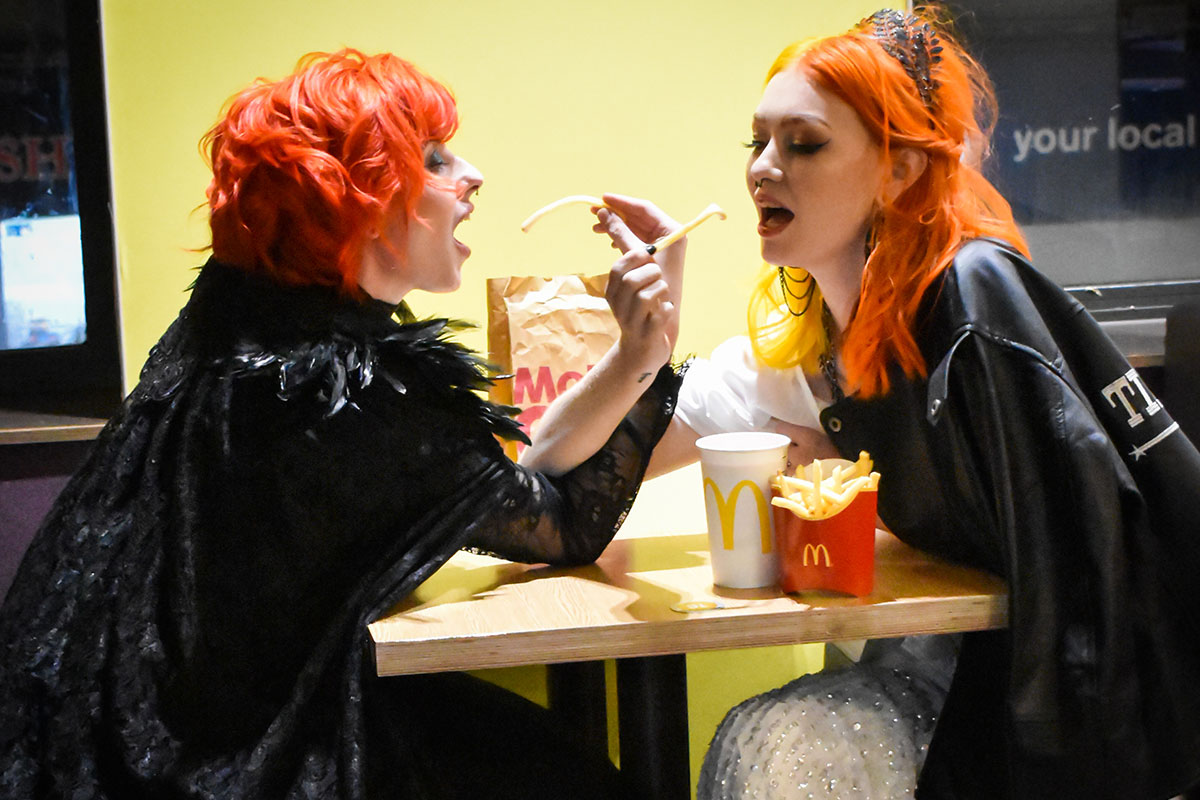 two brides wearing black and sharing chips at McDonalds Halloween wedding