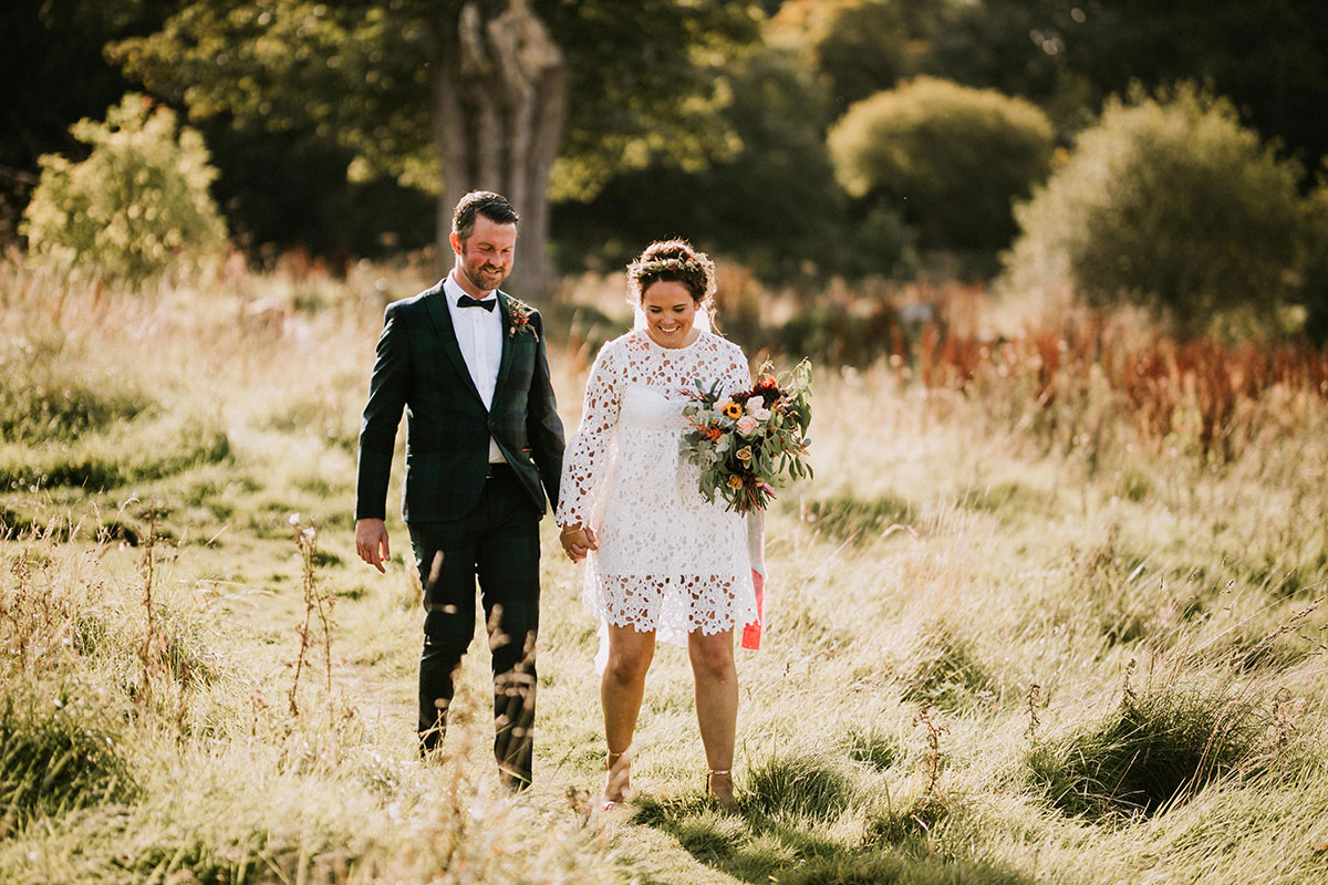 groom wearing ASOS black watch suit and bride wearing Boohoo wedding dress walking in grassland on a sunny day