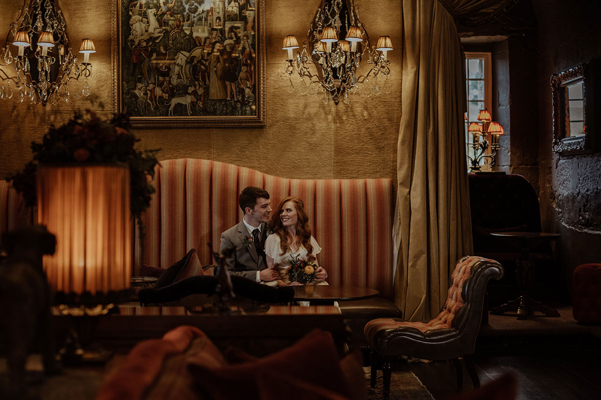 bride and groom sitting on striped sofa with ornate wall sconses above at Borthwick Castle