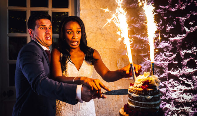 Bride and groom pulling funny faces while cutting a wedding cake topped with cake fountains that are alight