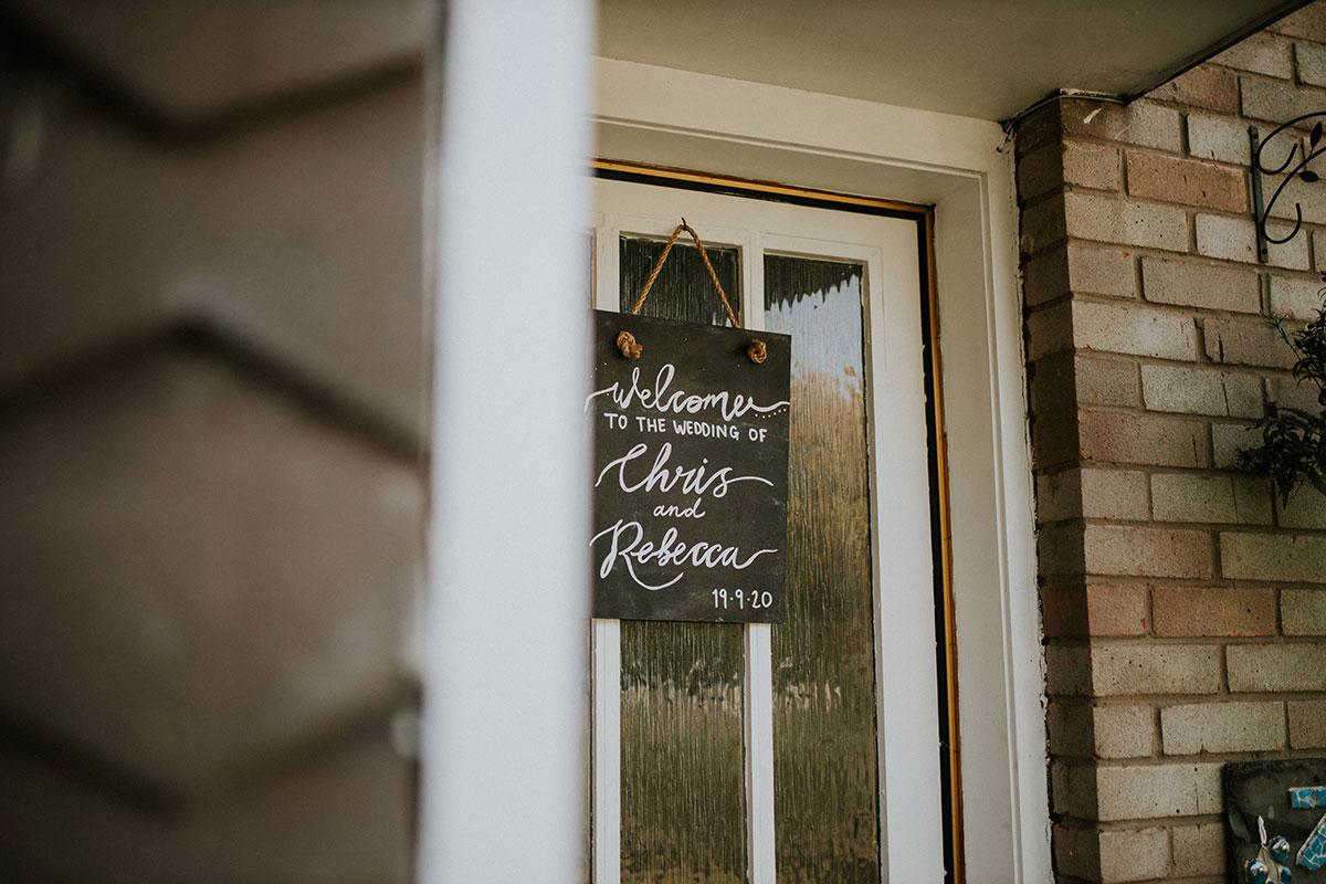 wedding blackboard welcome sign hanging on front door of house
