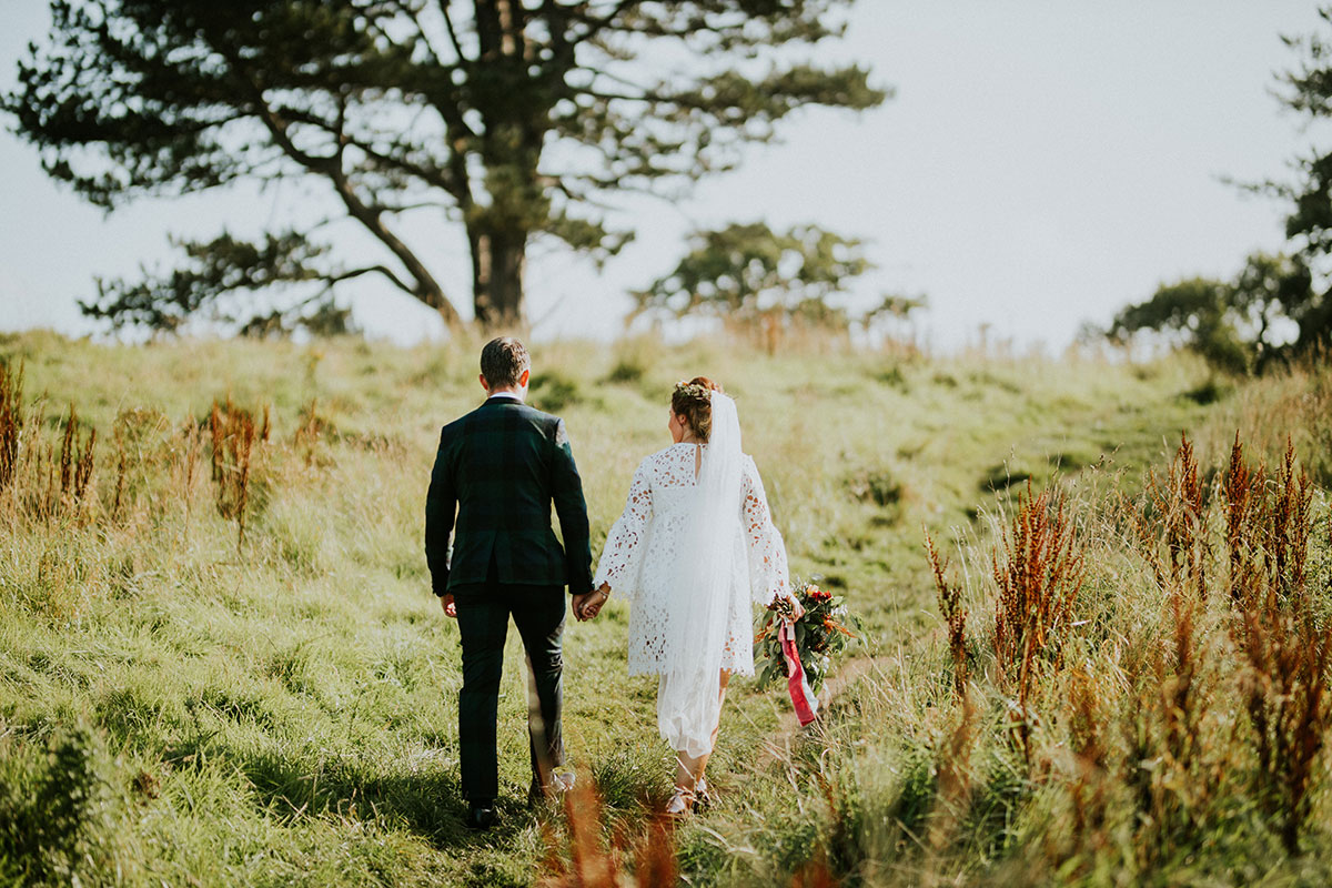 groom wearing ASOS black watch suit and bride wearing Boohoo wedding dress walking with back turned to camera in grassland on a sunny day