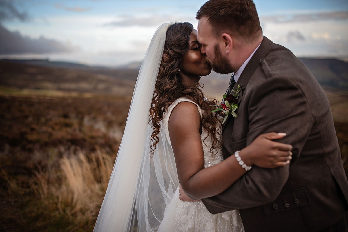 bride and groom kissing on moorland in Aberdeenshire captured by Karolina Kotkiewicz Photography