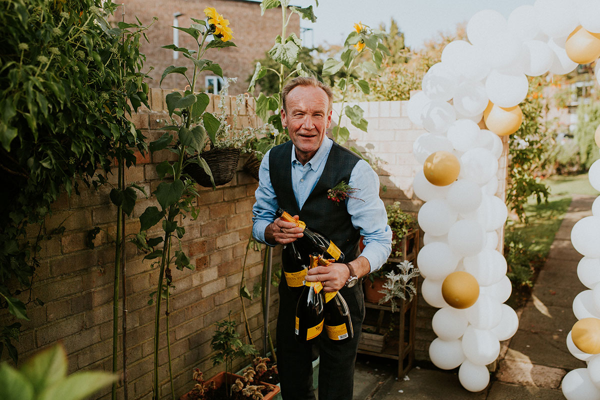 man wearing blue shirt and tweed waistcoat carrying 4 bottles of prosecco with balloon arch in background