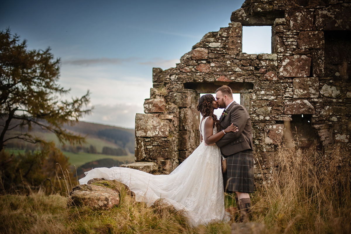 bride and groom kissing with ruined stone building in background