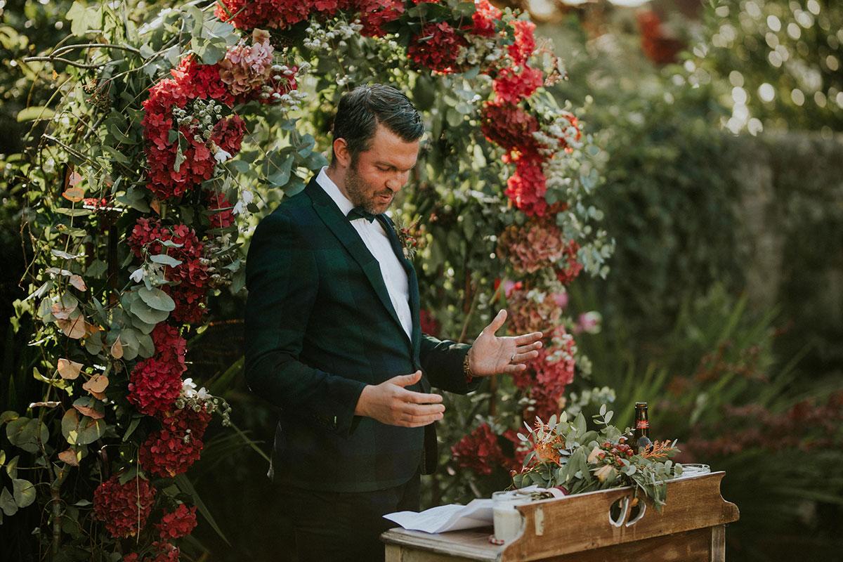 groom making speech in Edinburgh back garden with dark red hydrangea arch in back ground