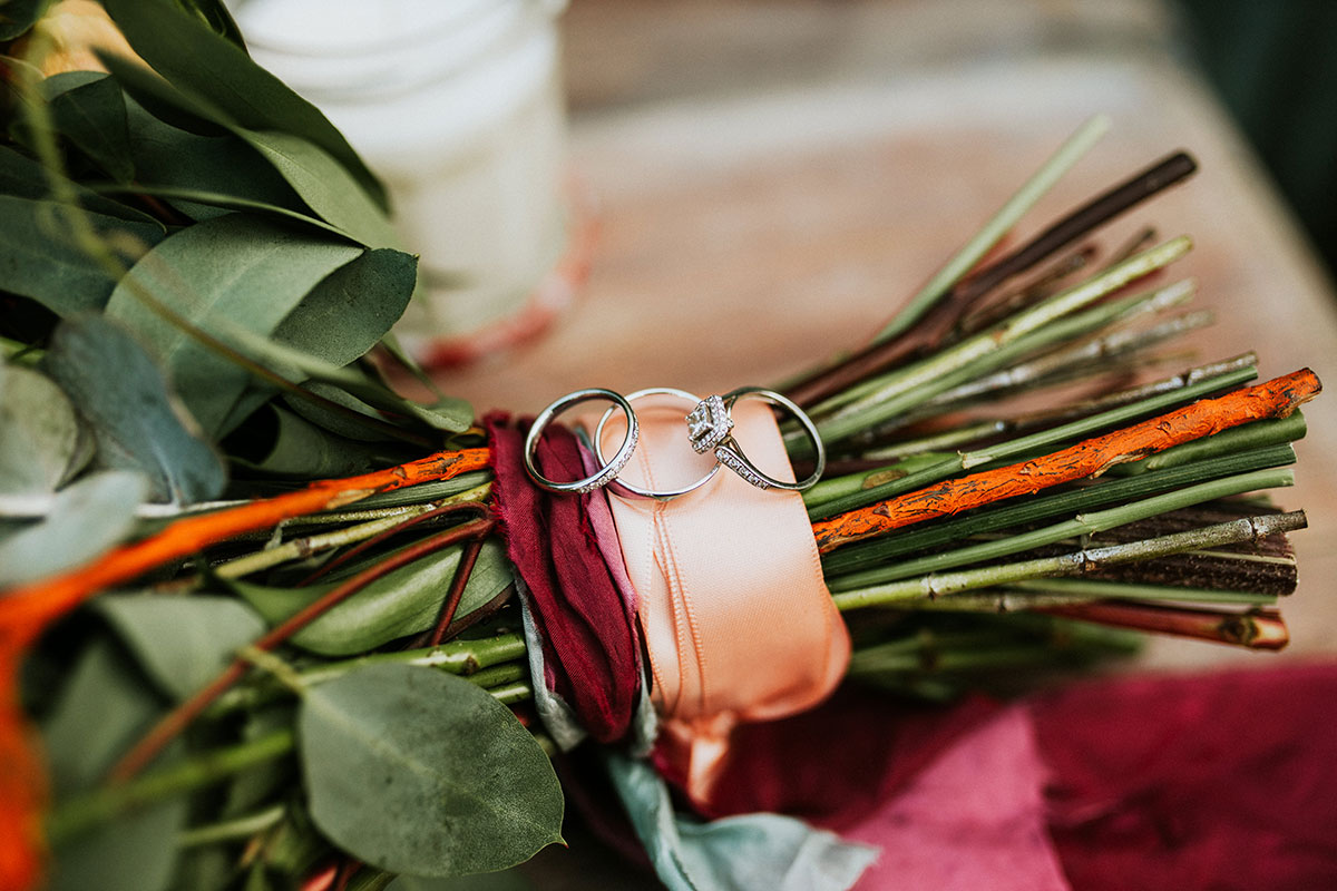 three platinum wedding and engagement rings sitting on bouquet ribbon and stems