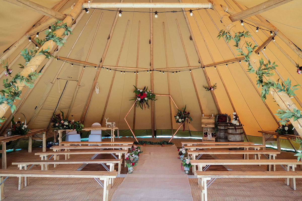 Below Canvas wedding tipi with wooden benches hexagon moongate and green ivy garland