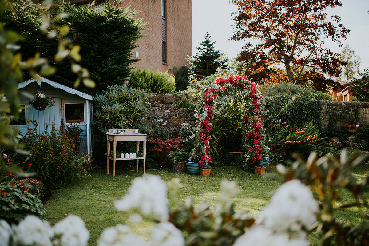 Edinburgh back garden set for a wedding with table and red floral arch