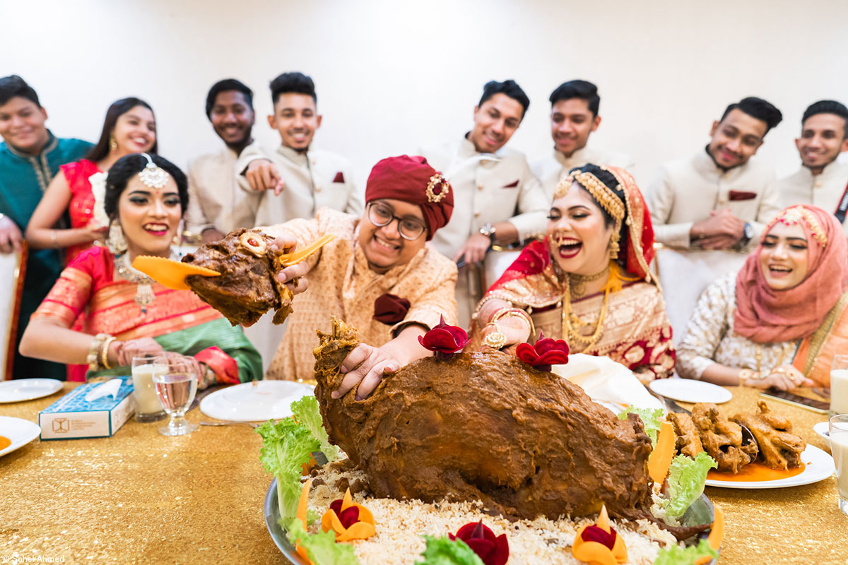 Laughing and smiling wedding guests carving a large piece of roasted meat at an Asian wedding