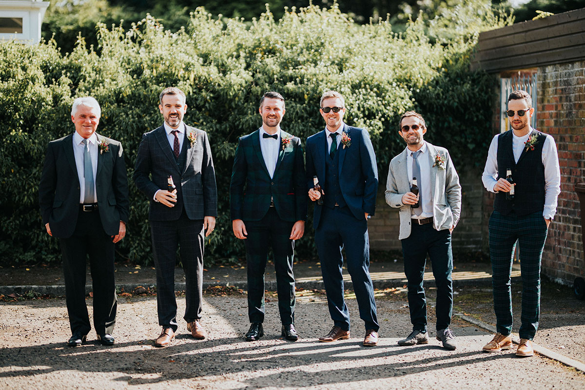 groom and five men standing with beers in hand ready for a wedding in an Edinburgh back garden