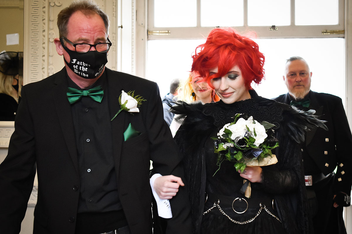 red haired bride wearing black being walked down aisle by man wearing father of the bride mask at a Halloween wedding at Chatelherault