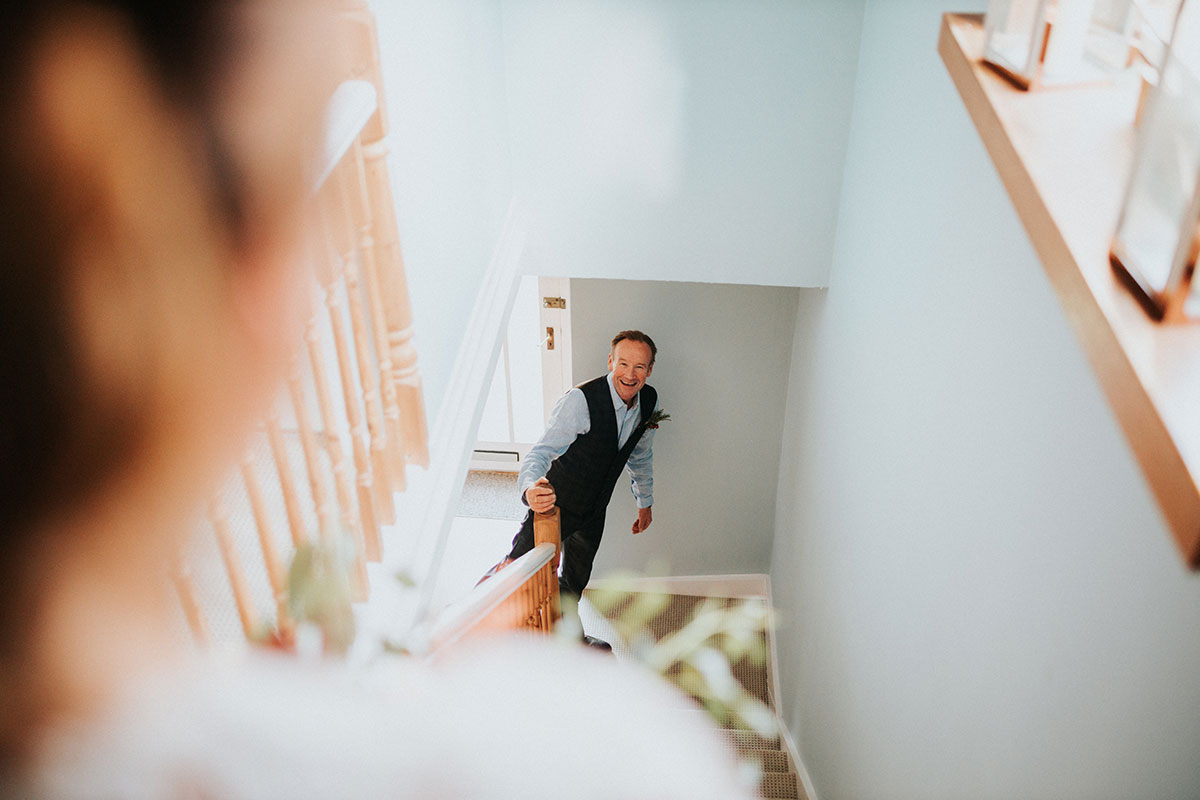 dad looking up stairs and seeing bride for the first time