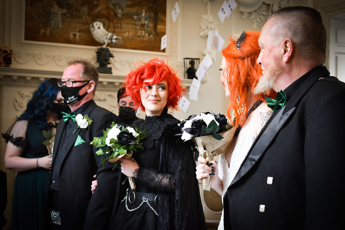 two brides at top aisle with fathers at Halloween wedding at Chatelherault
