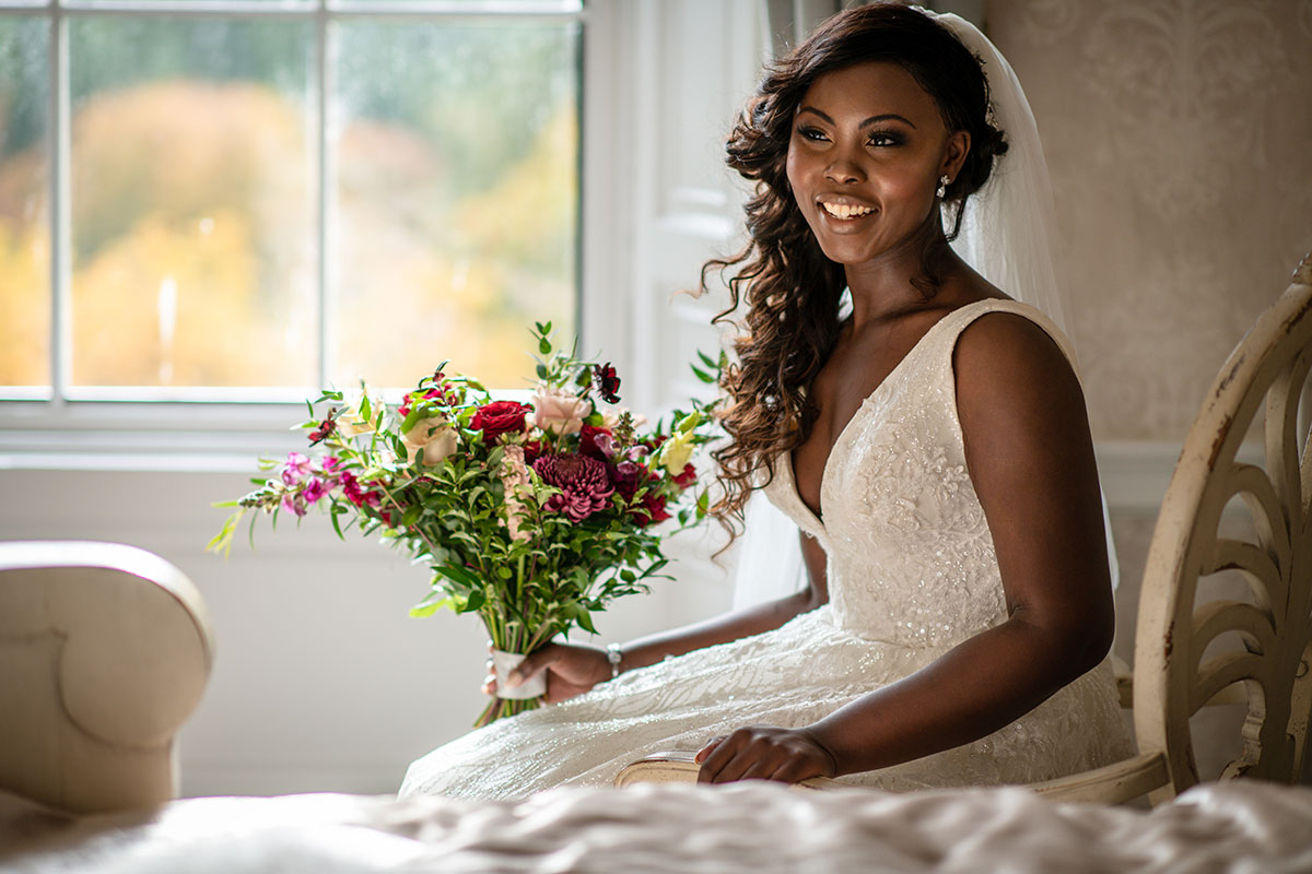bride sitting smiling on bed at Drumtochty Castle wearing dress by Avorio Bridal and carrying bouquet by Kim Dalglish