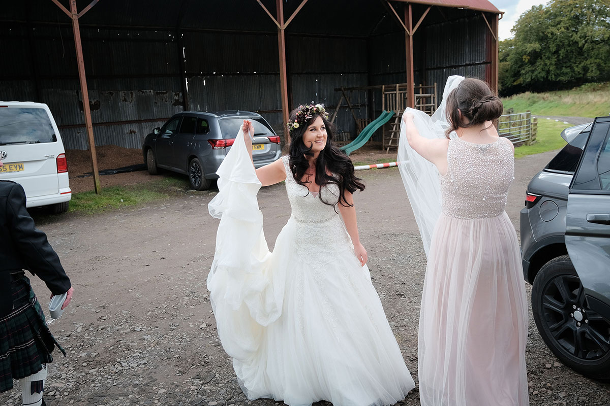 bride wearing dress by Wed2Be arriving at South Barlogan Farm with bridesmaid wearing pale pink glitter dress