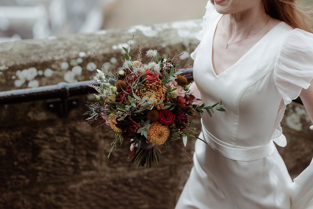 torso crop image of bride's Sanyukta Shrestha wedding dress and autumnal wedding bouquet by Narcissus Wedding Flowers