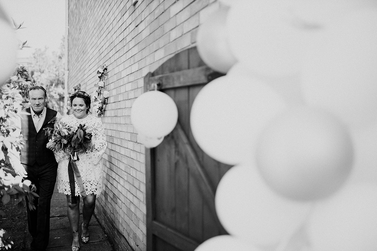 black and white image of bride and dad walking round side of house to back garden for wedding ceremony