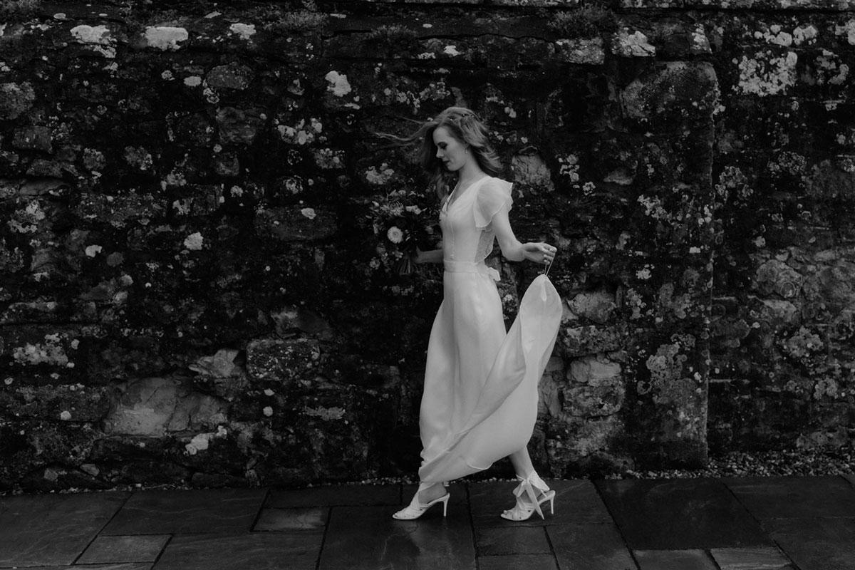 black and white image of bride walking past a stone wall at Borthwick Castle wearing Emmy Shoe and wedding dress by Sanyukta Shrestha