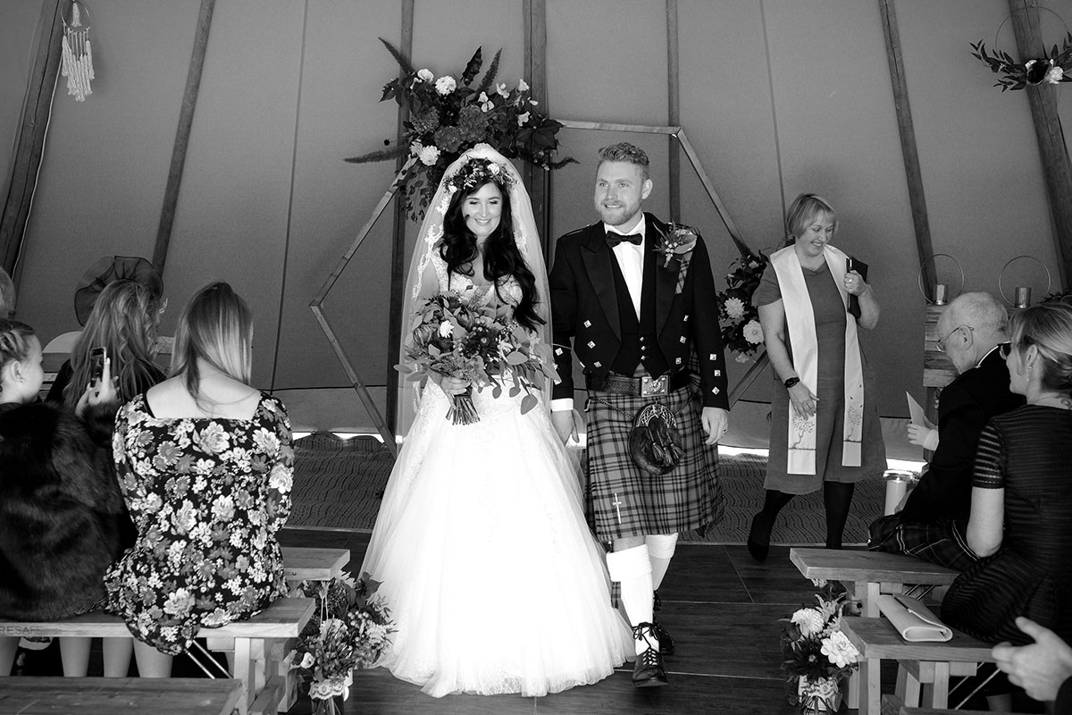black and white image of bride and groom walking up aisle just married in tipi at South Barlogan Farm
