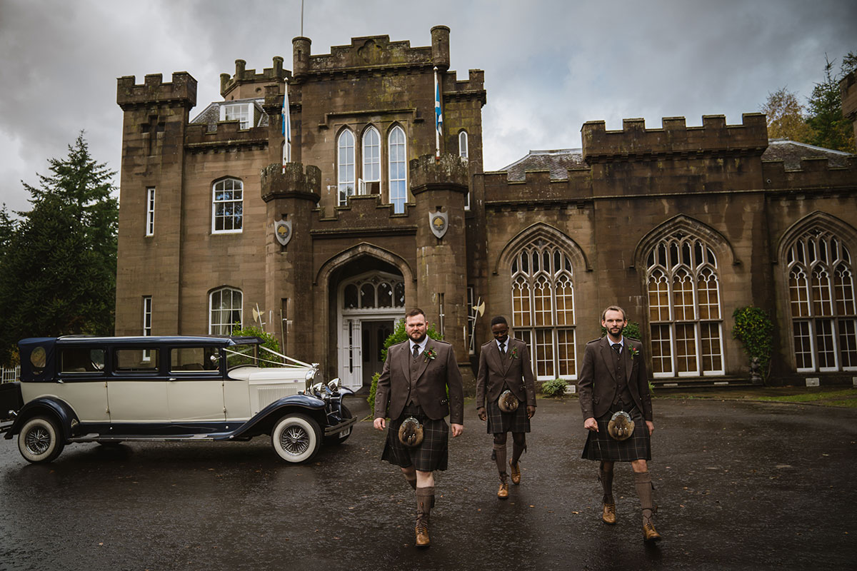 groom and two ushers wearing kilts walking outside Drumtochty Castle with vintage car from Silver City Wedding Cars parked in background