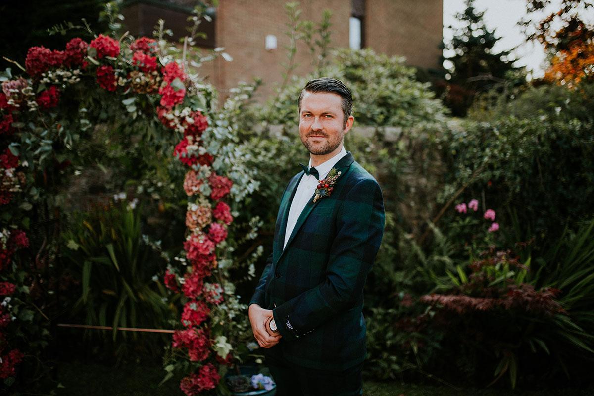 groom wearing ASOS black watch tartan suit standing next to red flower arch for Edinburgh back garden wedding ceremony