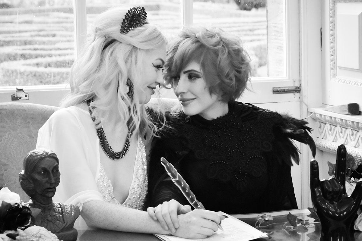 two brides signing register at Halloween wedding at Chatelherault