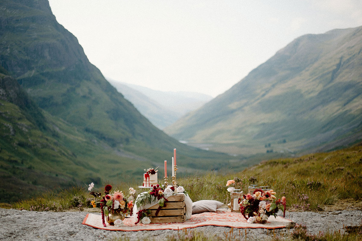 wild picnic wedding set up with candles, flowers and cake in Glen Coe Scotland