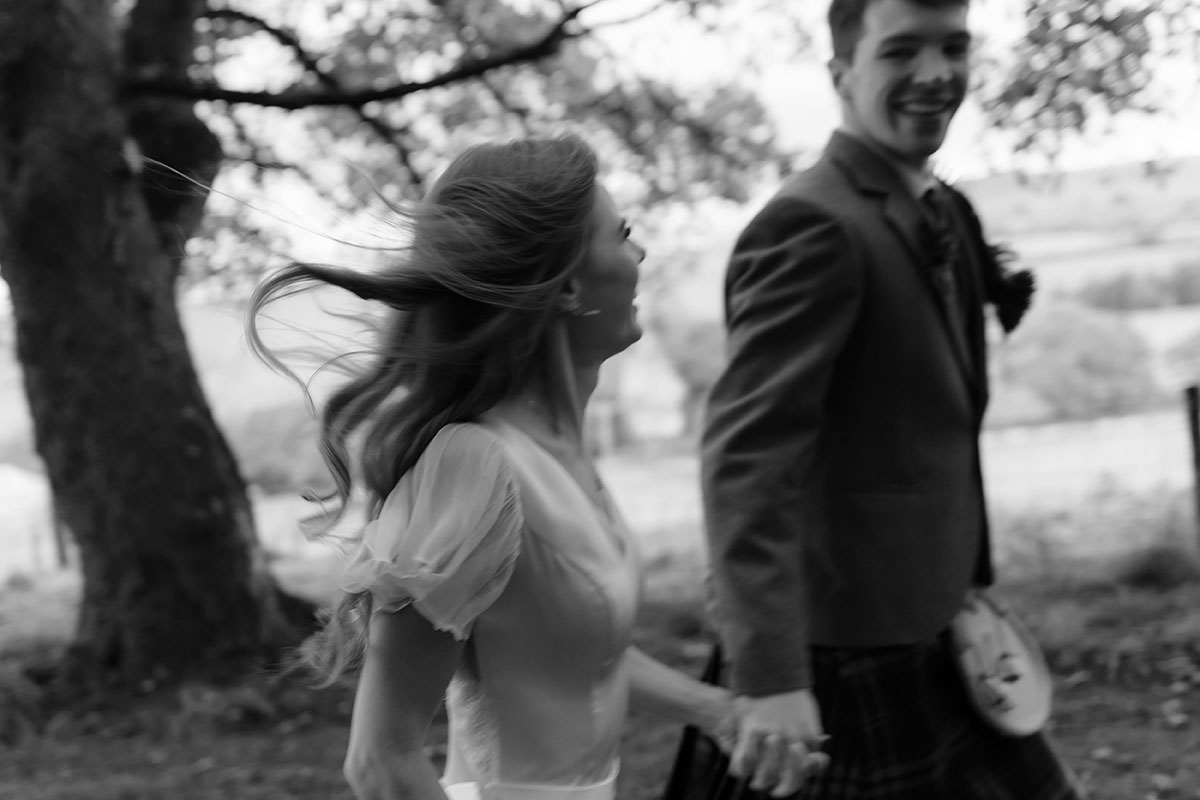 black and white image of bride and groom walking holding hands with tree and fields in backdrop at Borthwick Castle