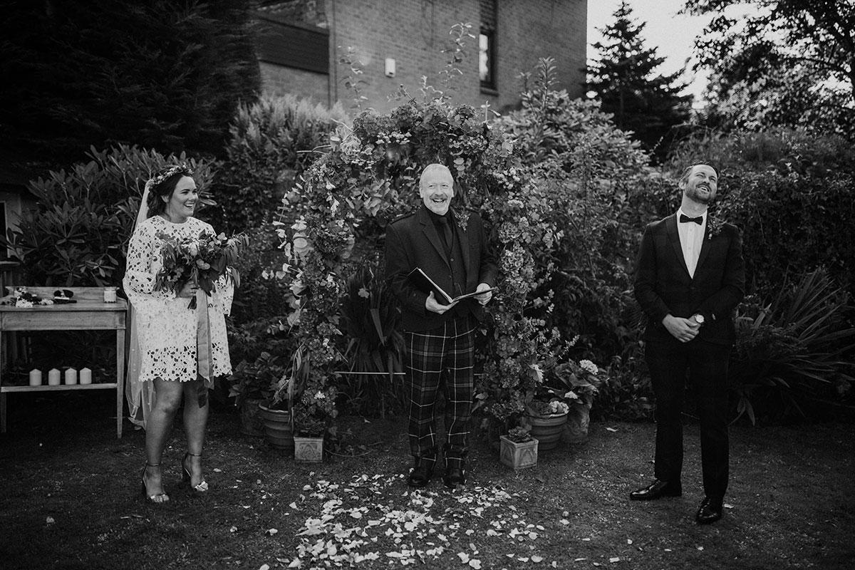 black and white image of bride, groom and wedding celebrant laughing at Edinburgh back garden wedding ceremony