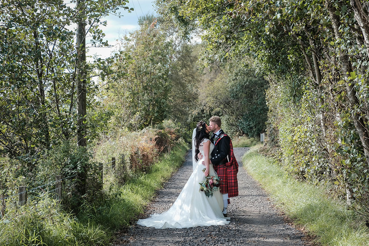 bride and groom kissing in middle of countryside road in Renfrewshire