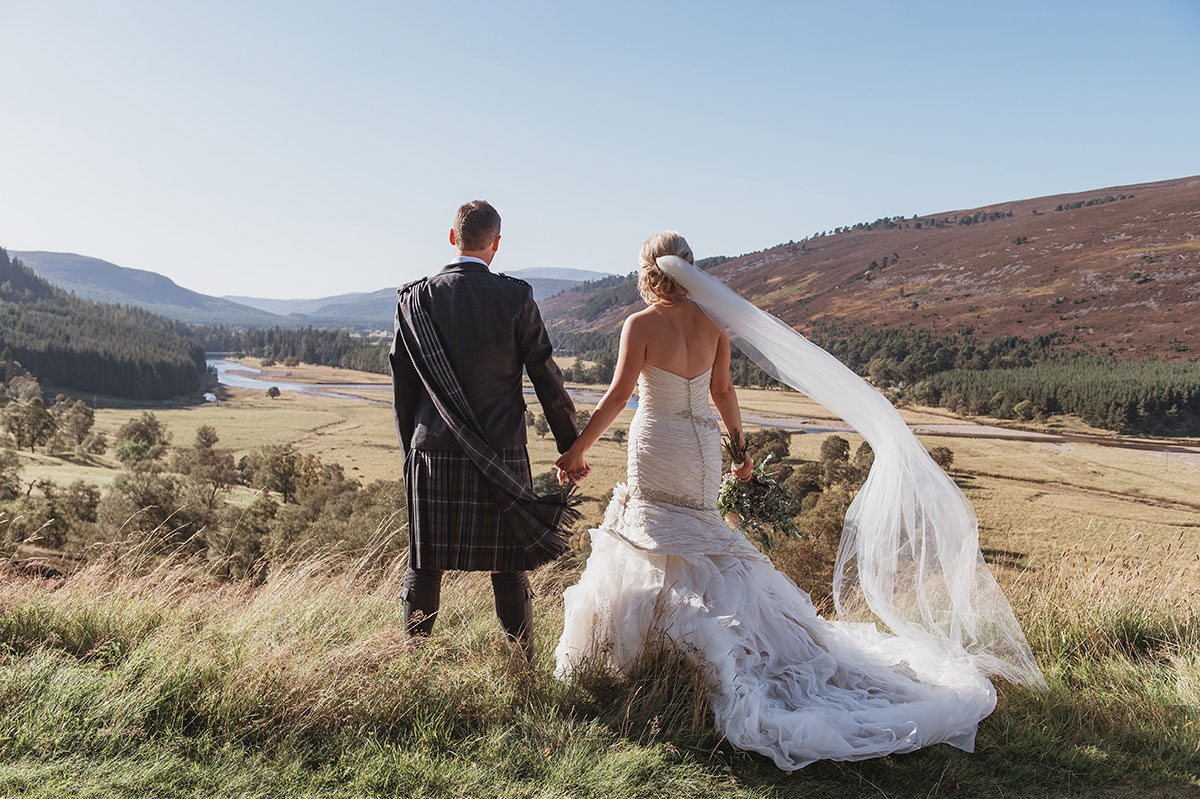 back of bride and groom looking out across Aberdeenshire countryside