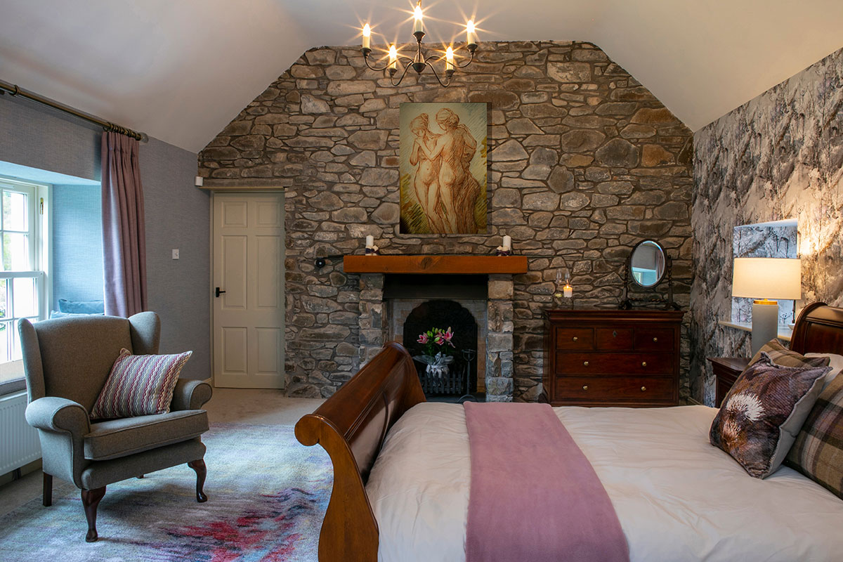 Bedroom with exposed rustic stone wall at Blackhouse Forest Estate
