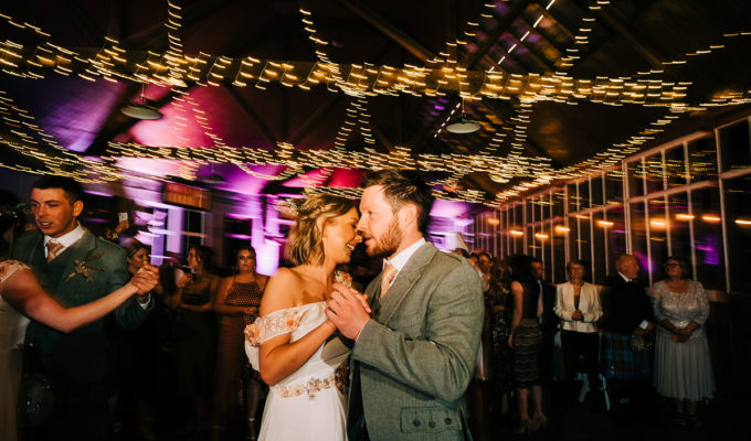 Man and woman dancing under lights at wedding as other guests watch on