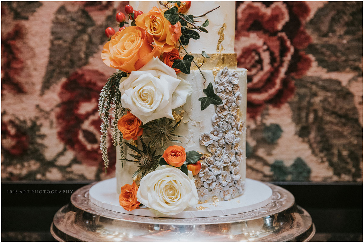Bottom detail of ornate gold-leaf and white and orange flower wedding cake by Ruby & Pearl Cake Art