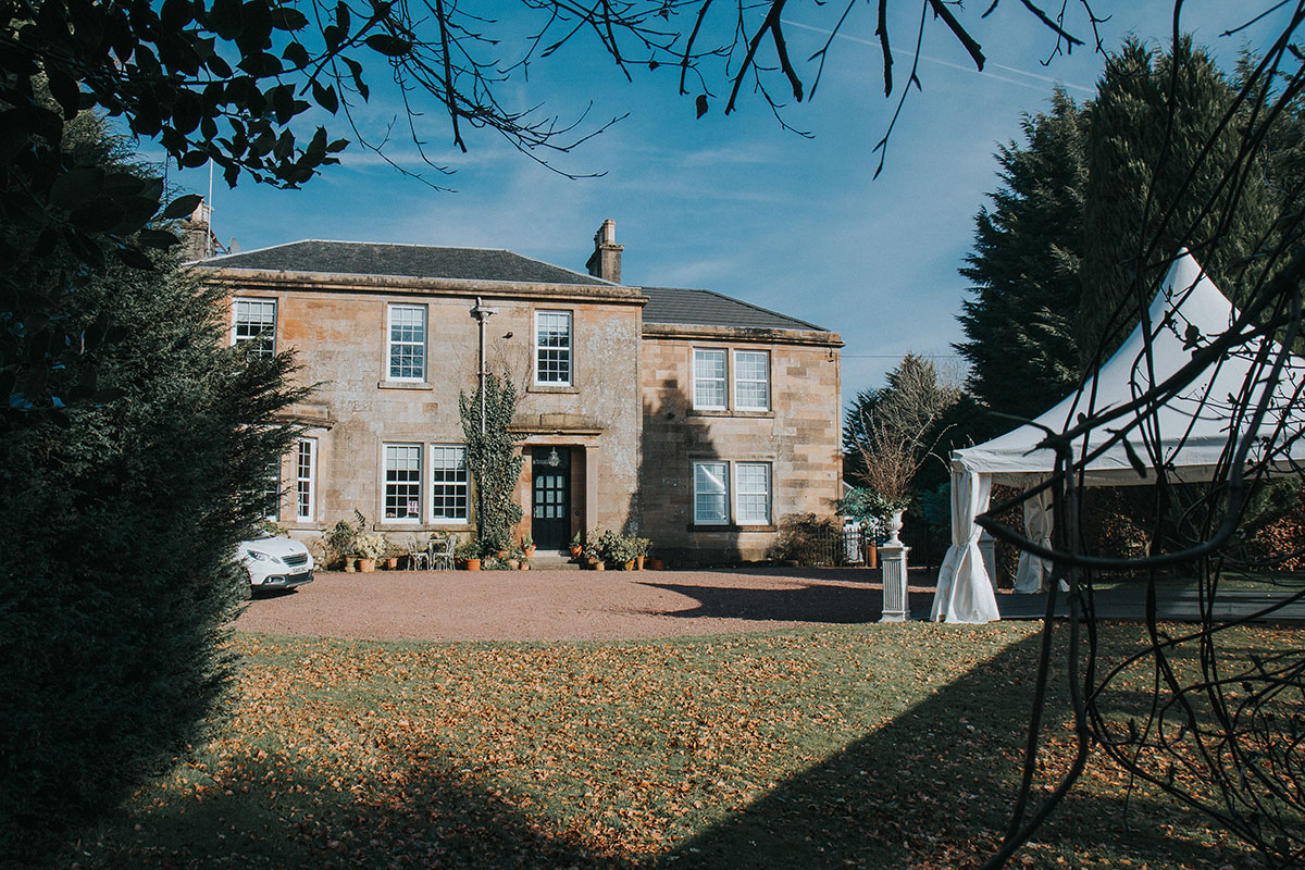 Front of a Georgian mansion in Scotland with small wedding marquee set outside on the right