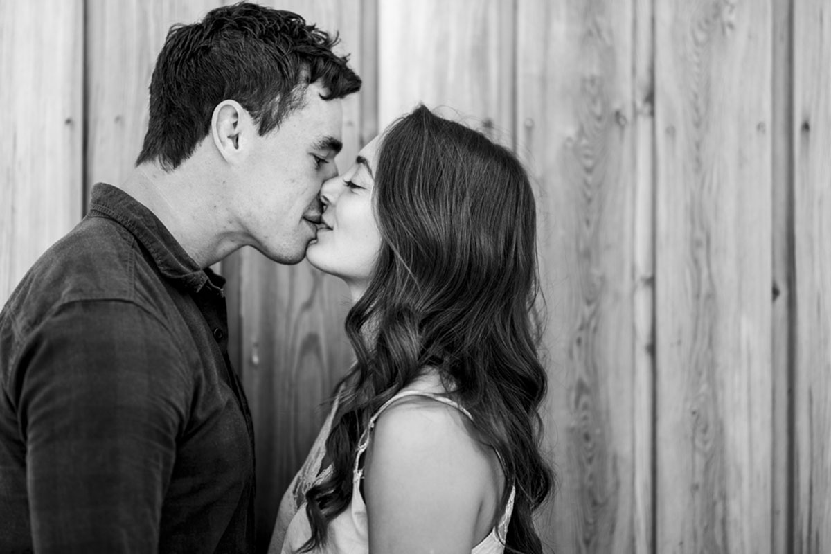 black and white photo of man and woman kissing against a wooden wall
