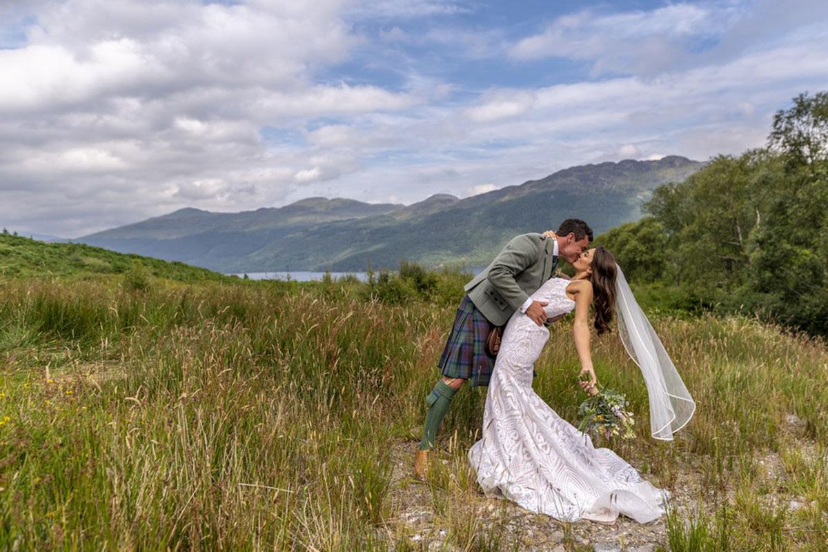 bride and groom kissing in Scottish landscape