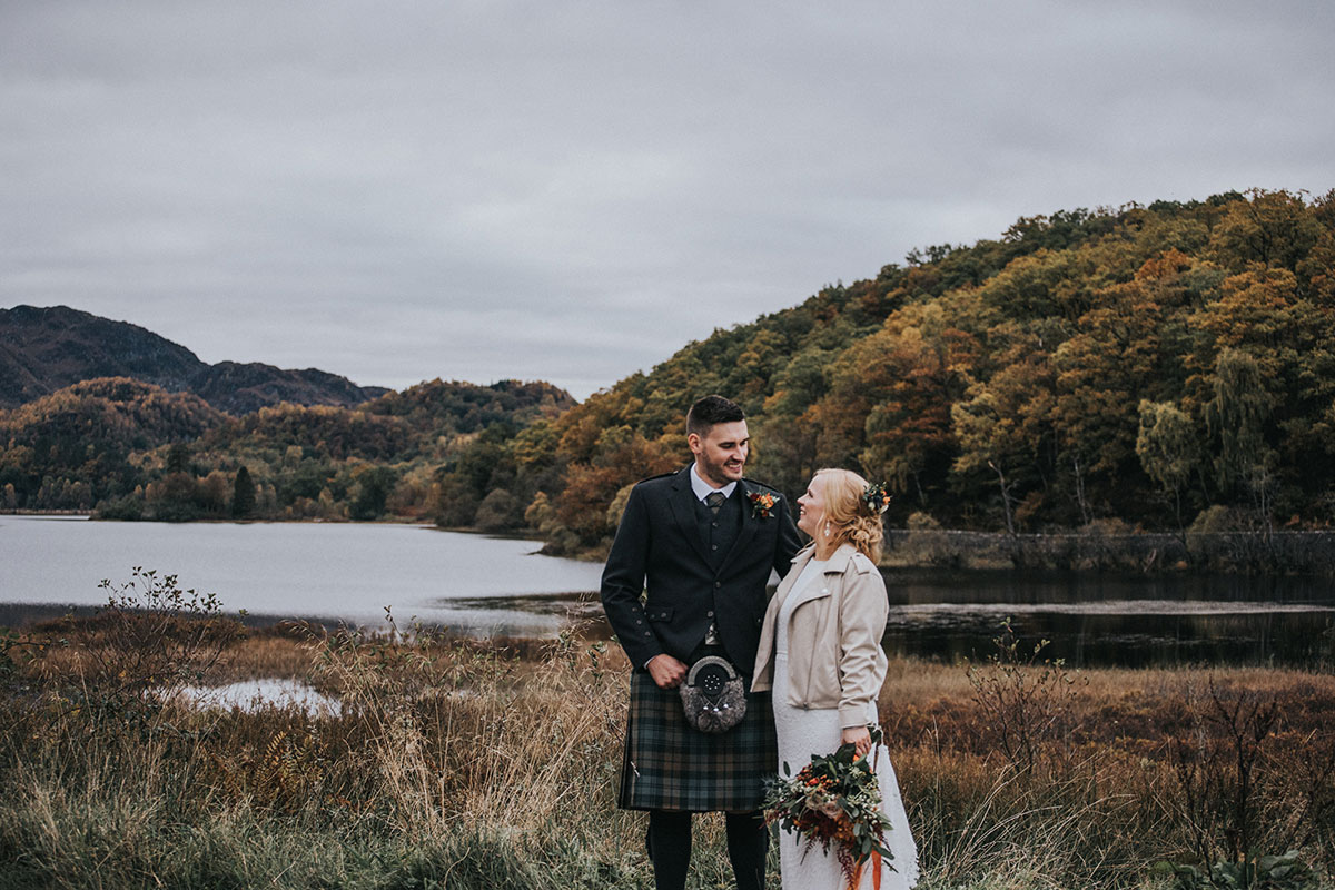 bride and groom standing by loch and woodland