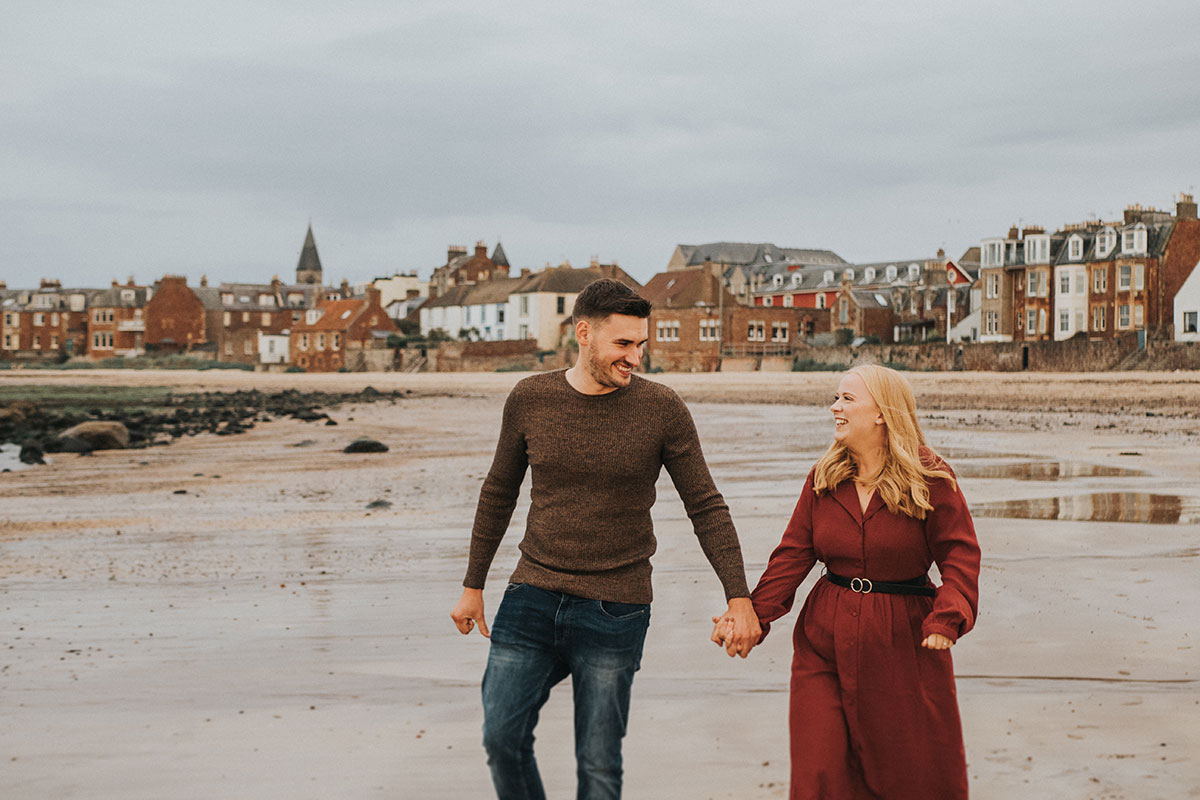 man and woman holding hands walking along beach in North Berwick