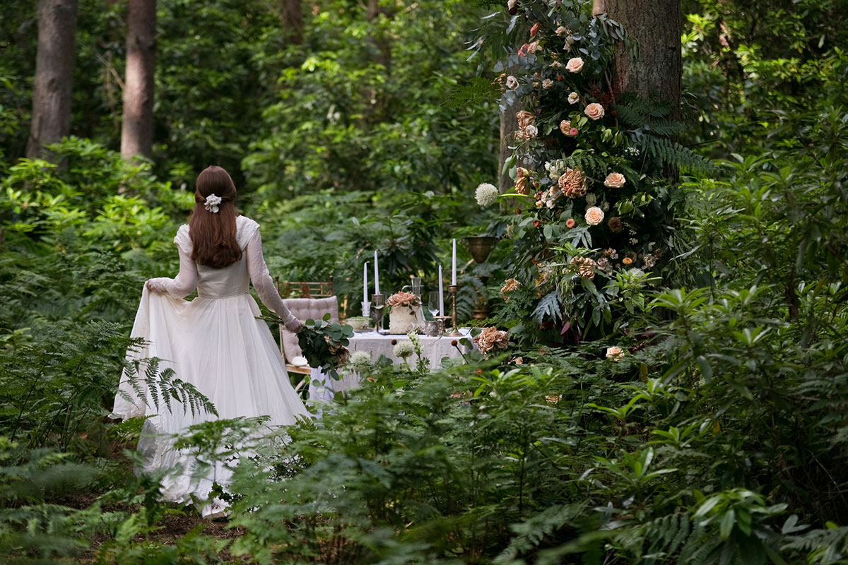 Back of bride in leafy forest setting walking towards a small outdoors dining table