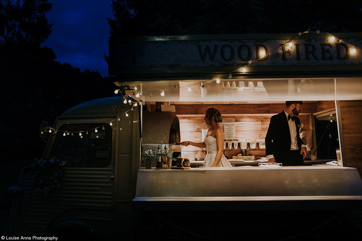 Bride and groom making pizza inside an pizza truck at nighttime