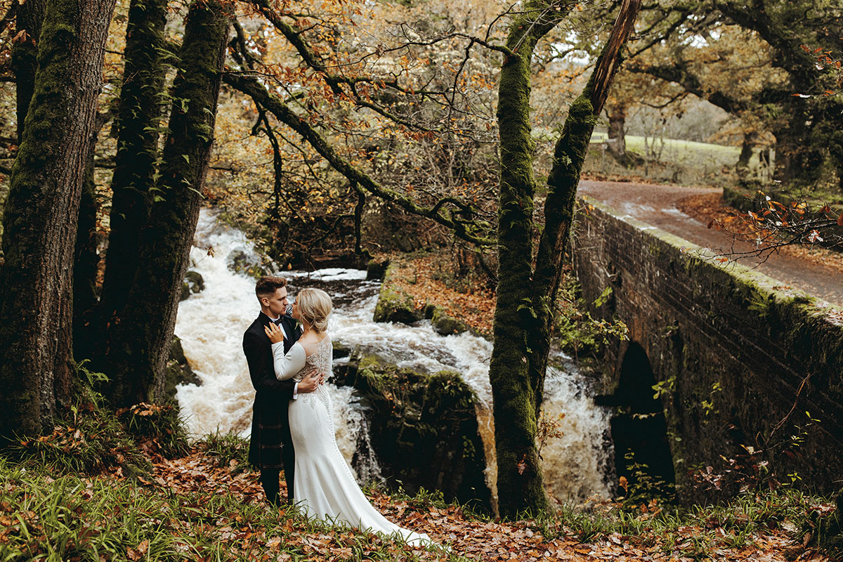 bride and groom in autumn woodland beside waterfall